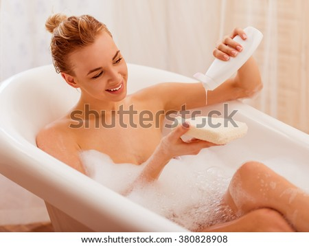 Beautiful young blonde woman enjoying pleasant bath with foam, putting shower gel on a wisp of bast and smiling - stock photo