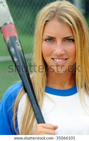 Beautiful young blonde woman holding softball bat over shoulder - stock photo