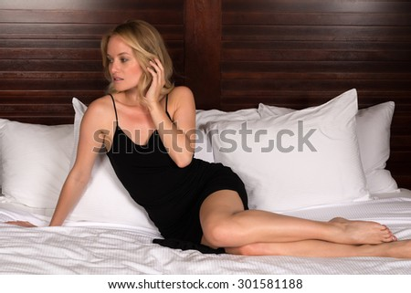Beautiful young blonde woman in a little black dress - stock photo