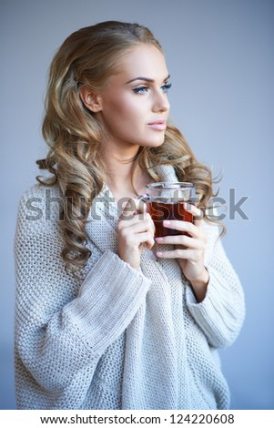 Beautiful young blonde woman in a stylish warm winter top standing daydreaming as she enjoys a mug of hot tea - stock photo