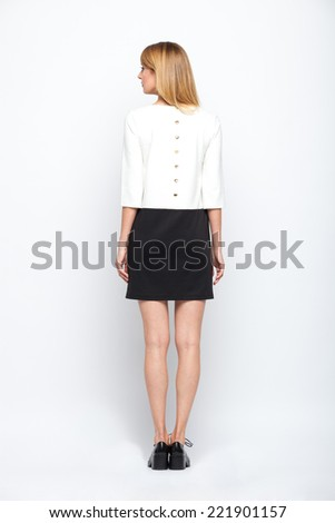 beautiful young blonde woman in black and white skirt standing on grey background