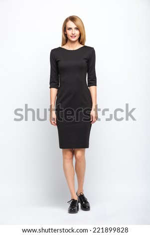 beautiful young blonde woman in black skirt standing on grey background - stock photo