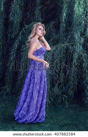 Beautiful young blonde woman in luxury dress posing in front of magical forest - stock photo