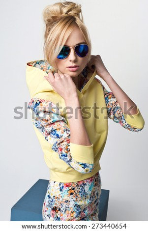 beautiful young blonde woman in nice fashionable clothes, hoodie, sunglasses posing in studio. Fashion photo - stock photo