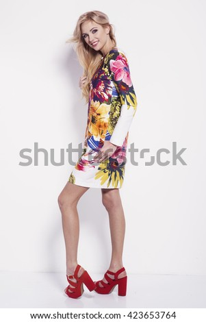 beautiful young blonde woman in nice spring coat, handbag, red shoes posing in a studio. Fashion spring summer photo - stock photo