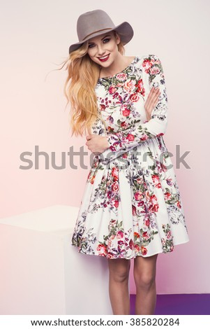 beautiful young blonde woman in nice spring dress, hat and holding a handbag posing  in studio. Fashion photo - stock photo