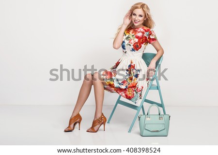 beautiful young blonde woman in nice spring dress, high heels shoes handbag posing in a studio. Fashion spring summer photo - stock photo