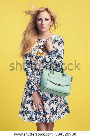 beautiful young blonde woman in nice spring dress, holding a handbag posing on yellow background in studio. Fashion photo - stock photo