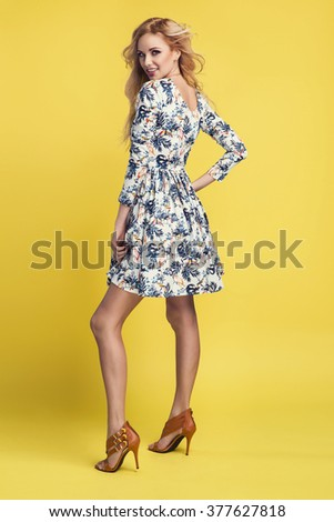 beautiful young blonde woman in nice spring dress, posing on yellow background in studio. Fashion photo - stock photo