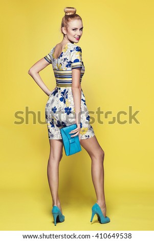 beautiful young blonde woman in nice spring dress, posing on yellow background in studio. Fashion photo, blue handbag and high heels shoes - stock photo
