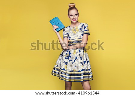 beautiful young blonde woman in nice spring dress, posing on yellow background in studio. Fashion photo, purse - stock photo