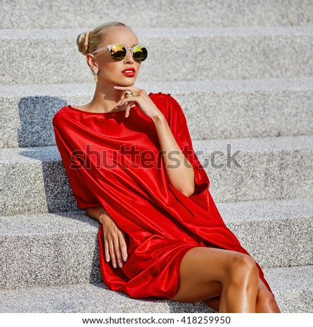 Beautiful young blonde woman in red dress and sunglasses outdoor street fashion portrait - stock photo