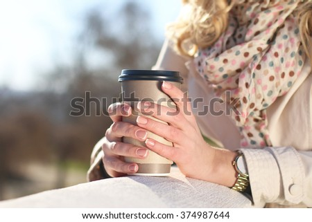 Beautiful young blonde woman in trench coat outdoor with coffee to go cup