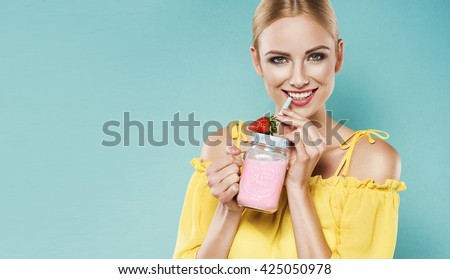 Beautiful young blonde woman in yellow top drinking strawberry smoothie with a straw in a summer day. Healthy organic drinks concept. People on a diet. - stock photo