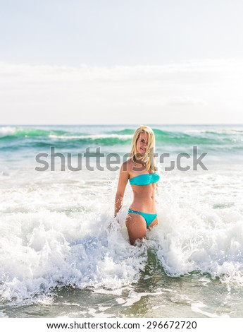 beautiful young blonde woman jumping in big waves in the blue sea bright day in the resort in Europe - stock photo