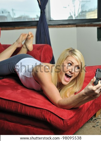 Beautiful young blonde woman lounging on red chaise lounge (chaise longue) chair in white tank top and and gray athletic pants smiling as she takes a picture of herself with a smartphone - stock photo