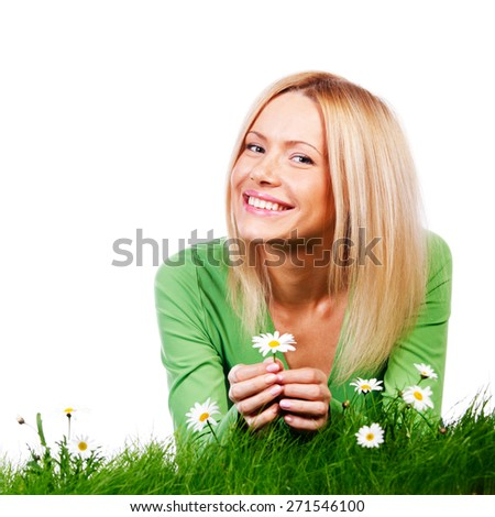 Beautiful young blonde woman lying on grass with chamomile flowers, isolated on white background
