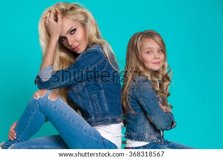 beautiful young blonde woman mom with a daughter sitting on a chair in  denim jackets, jeans sports shoes sneakers trainers reversed back to back and cheerfully tenderly smiling and form a family