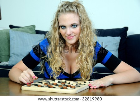 Beautiful young blonde woman playing checkers