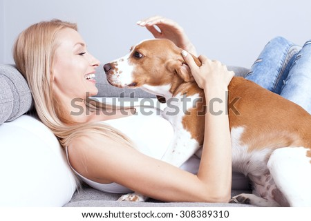 Beautiful young blonde woman playing with her dog at home, smiling. Happiness.