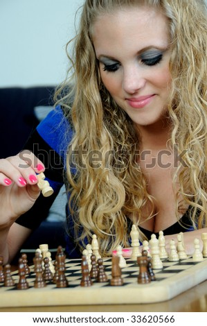 Beautiful young blonde woman playing wooden chess game