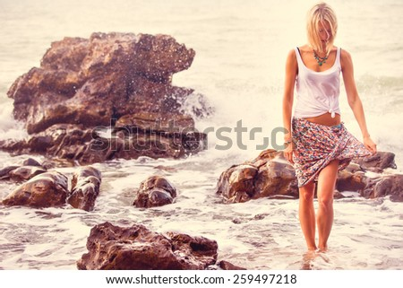 Beautiful young blonde woman posing outdoor at the rocky sea shore. Trendy fashion female model dressed in white top and mottled skirt  - stock photo