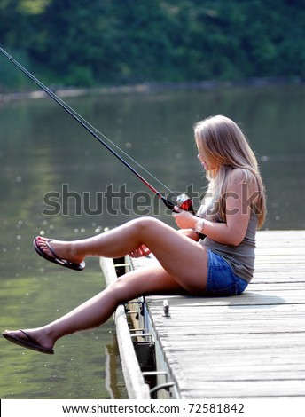 Beautiful young blonde woman scratches her leg while fishing from a pier - stock photo