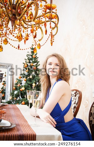 Beautiful young blonde woman sitting at the table with glass of champagne - stock photo