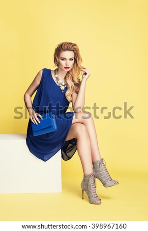Beautiful young blonde woman sitting in a trendy shoes, blue dress big necklace. Fashion photo on yellow background. - stock photo