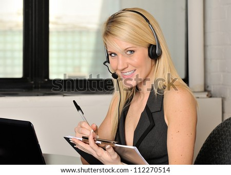 Beautiful young blonde woman sitting in office wearing a telephone headset and writing on clipboard as she talks