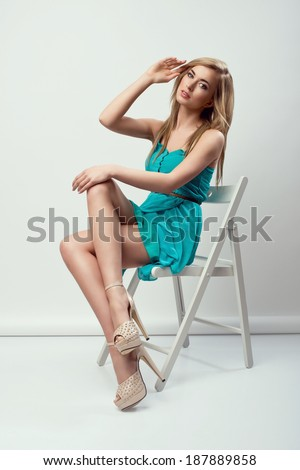Beautiful young blonde woman sitting on a chair, in a blue dress  - stock photo