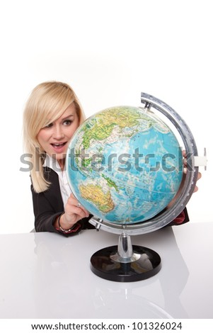 Beautiful young blonde woman sitting studying a world globe and planning her dream holiday