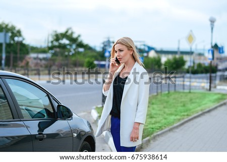 Beautiful young blonde woman speaking speaking on phone near black car.