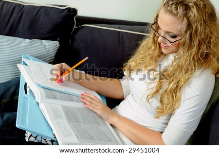 Beautiful young blonde woman studying at home with lap desk