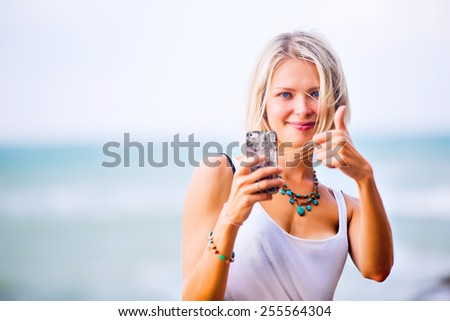 Beautiful young blonde woman taking a selfie on smart-phone outdoor at the rocky sea shore. Trendy fashion female model dressed in white top - stock photo