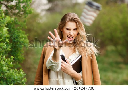 Beautiful young blonde  woman throwing away coffee outdoors - stock photo