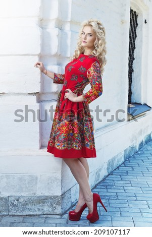 Beautiful young blonde woman walking around the city streets. Outdoors shot.