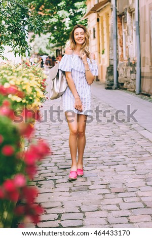 beautiful young blonde woman walking on the street and talking on a cell phone,the girl laughs and smiles,the perfect photo for mobile advertising travel,shopping for magazines,photo -style lifestyle