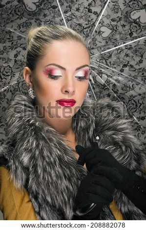Beautiful young blonde woman wearing a fur and holding an umbrella. umbrella is a background