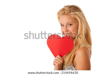 Beautiful young blonde woman with blue eyes holding red hart banner for valentine's day isolated over white