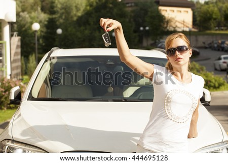 Beautiful young blonde woman with car key in hand - stock photo