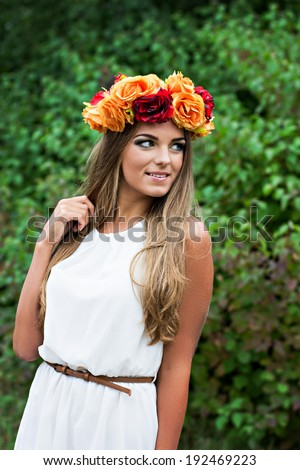 beautiful young blonde woman with flower wreath on his head in the garden