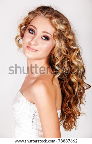 Beautiful young blonde woman with long curly hair in white fashion sequin top isolated on white background. - stock photo
