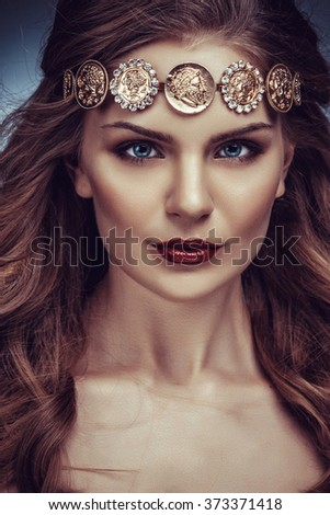 Beautiful young blonde woman with long hair with a diadem in the Greek style.