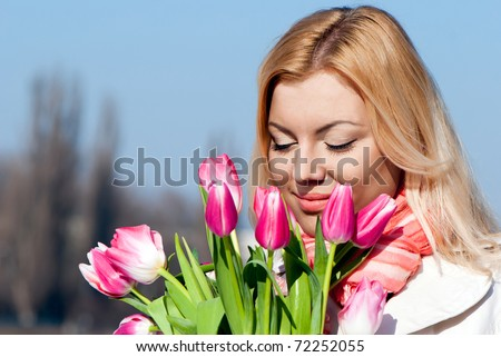 Beautiful young blonde woman with pink tulips - stock photo