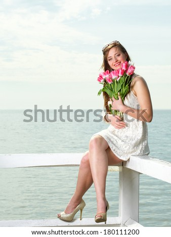 Beautiful young blonde woman with pink tulips blue sea and sky - stock photo