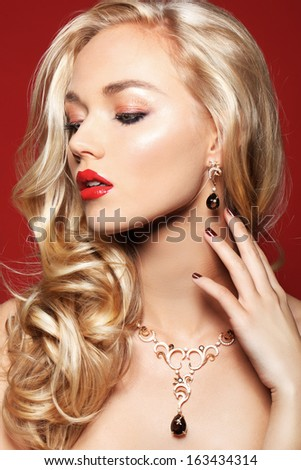 Beautiful young blonde woman with red lipd and manicure on red background, perfect skin - stock photo