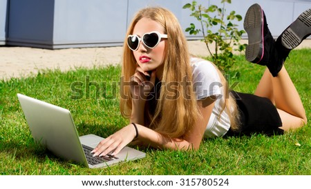 Beautiful young blonde woman working with her notebook lying on a lawn.young beautiful woman using a laptop computer in the park.Pretty student girl with laptop studying in the park on green grass.  - stock photo