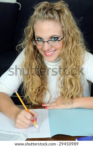 Beautiful young blonde woman writing in blue exam book - stock photo