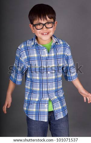 Beautiful young boy making a goofy face with silly glasses looking like a nerd on a grey background